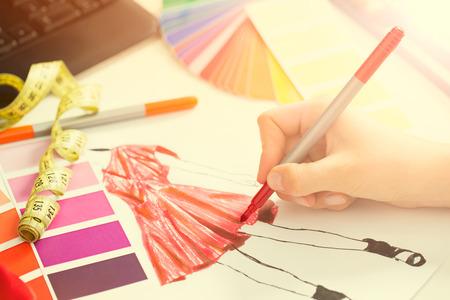 moda: Fashion designer lavora in studio. Primo piano del design.