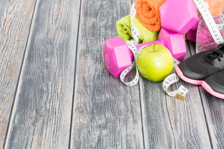competition: Fitness equipment and healthy nutrition on wood background.