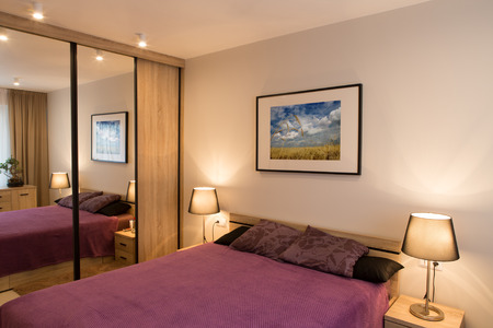 bedside lamp: Luxury modern style bedroom. Purple bed and bedside lamp.