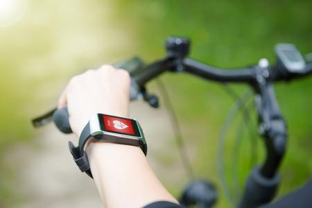 Mujer que monta una bicicleta con un monitor de frecuencia cardiaca SmartWatch. Concepto de vigilancia inteligente. Foto de archivo - 43398553