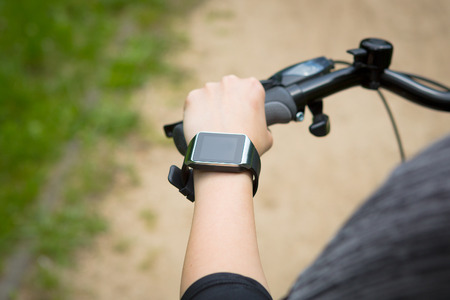 sports gear: Woman riding a bike with a SmartWatch heart rate monitor. Smart watch concept.