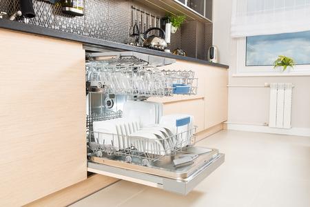 Open vaatwasser met schone keukengerei erin. Stockfoto