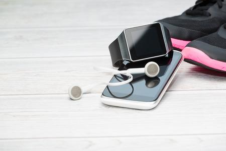 tecnologia: equipamentos de ginástica, relógio inteligente e telefone no fundo de madeira.