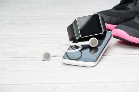 Fitness equipment, smart watch and phone on wood background. Stockfoto