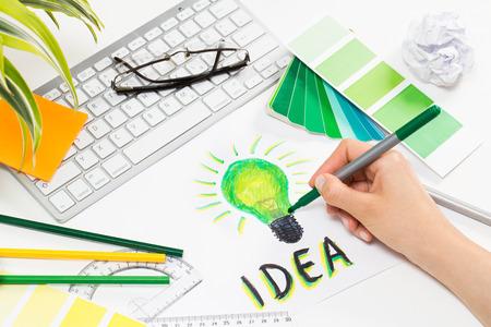 Designer Zeichnen eines grünen Glühbirne. Brainstorming und Inspiration cocnept. Lizenzfreie Bilder
