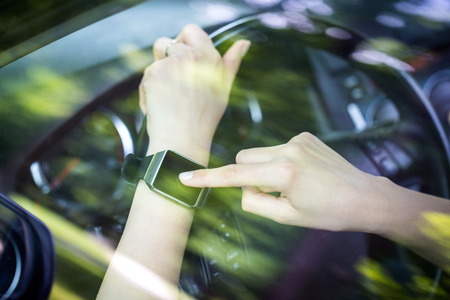 portable information device: A woman uses smartwatch in the car. Smart watch concept.