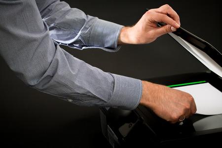 mfp: Man using scanner multifunction device on black background.