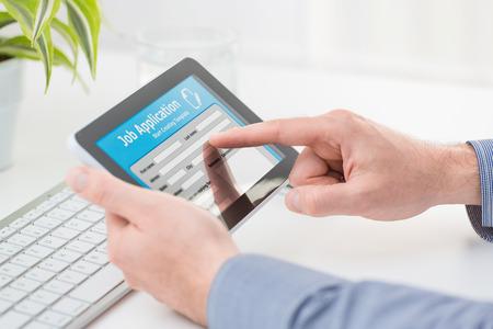 Demandeur remplissant la demande d'emploi en ligne par tablette numérique. Banque d'images