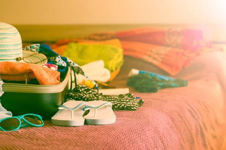 suitcase packing: Open suitcase with clothing in the bedroom. Summer holiday concept.