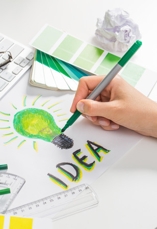 designer: Designer drawing a green light bulb. Brainstorming and inspiration cocnept.