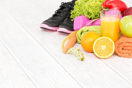 Fitness apparatuur en gezonde voeding op hout achtergrond.