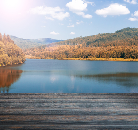 lake sunset: Empty wooden pier with mountain lake in the background.