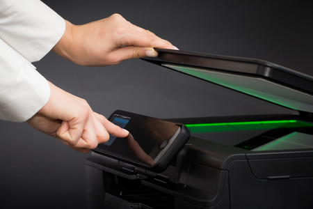 copier: Woman using scanner multifunction device on black background.