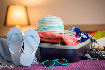 vacation: Open suitcase with clothing in the bedroom. Summer holiday concept.