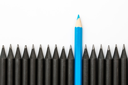 Blue pencil standing out from the row of black pencils. Reklamní fotografie - 50912644