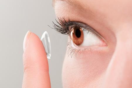 그녀의 눈에 콘택트 렌즈를 삽입 여자.