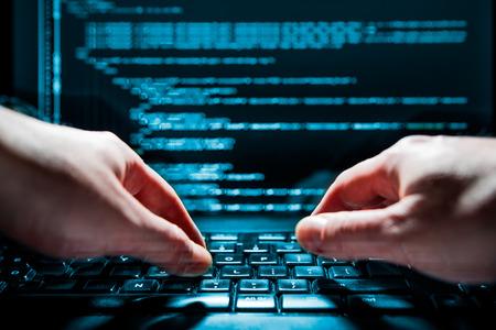 virus informatico: Hacker usando la computadora port�til. Un mont�n de d�gitos en la pantalla del ordenador. Foto de archivo