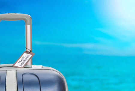 travel background: Suitcase with travel insurance label on blurred sea background.