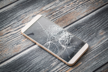 Modern broken mobile phone on wooden background. Stock Photo