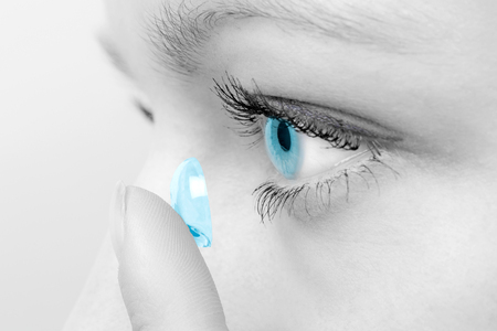 Mujer que inserta una lente de contacto en su ojo.