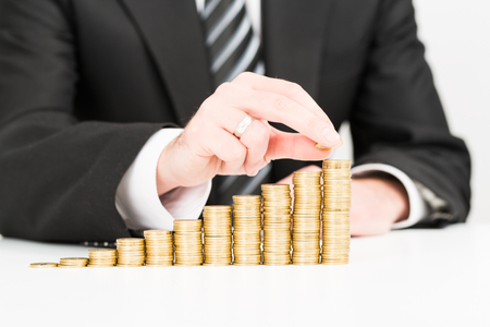 growing business: Saving money concept. Businessman hand putting money coin stack growing business.