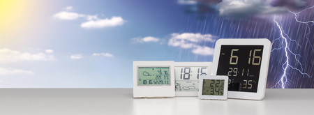 Weather station device with weather conditions outside background.