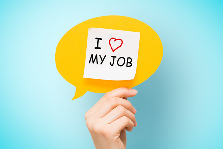 "Adhesive note on yellow speech bubble with ""I love my job"" words on blue background."