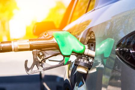 fuelling station: Arma de gasolina en el tanque se llene. concepto de reabastecimiento de combustible del coche. Foto de archivo