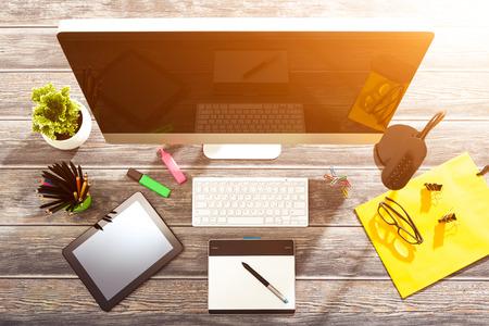 travail de bureau avec tablette et pc sur table en bois.