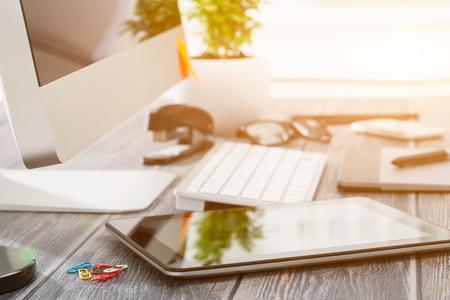 Kancelářské pracoviště s tablet a PC na dřevěném stole. Reklamní fotografie