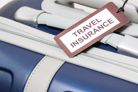 holdall: Travel insurance label tied to a suitcase.
