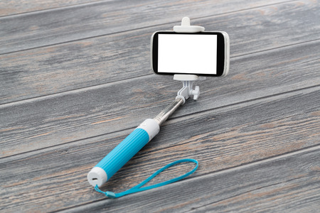 extensible: Smart phone on a selfie stick on wooden background. Stock Photo