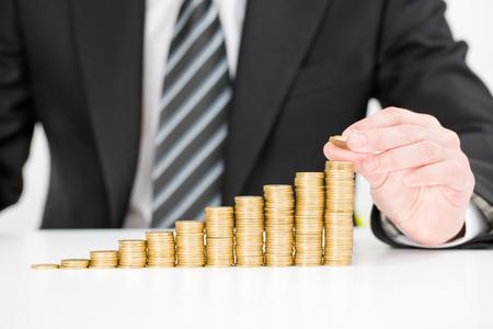 Concepto de ahorro de dinero. Mano del hombre de negocios que pone negocio creciente de la pila de la moneda del dinero. Foto de archivo