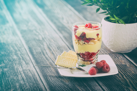 mascarpone: Tasty mascarpone dessert in glass with biscuit, raspberries fruit on wooden background.