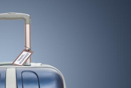 Koffer mit Reiseversicherung Etikett auf blauem Hintergrund. Standard-Bild