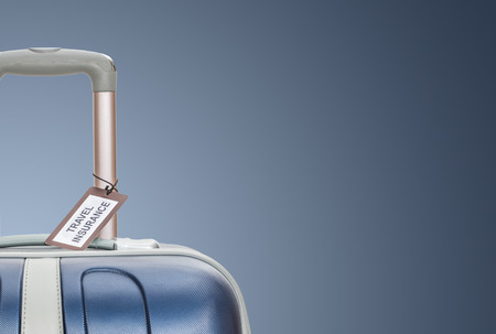 Suitcase with travel insurance label on blue background.