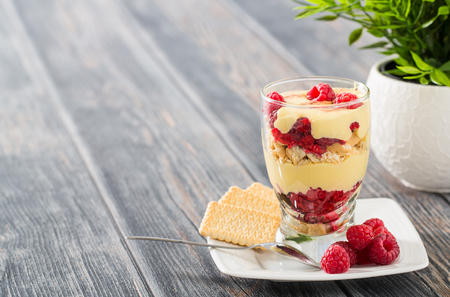 biscuits: Tasty mascarpone dessert in glass with biscuit, raspberries fruit on wooden background.