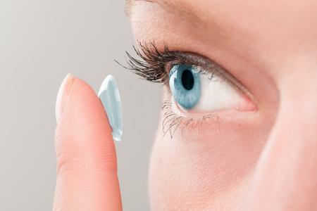 Mujer que inserta una lente de contacto en su ojo. Foto de archivo