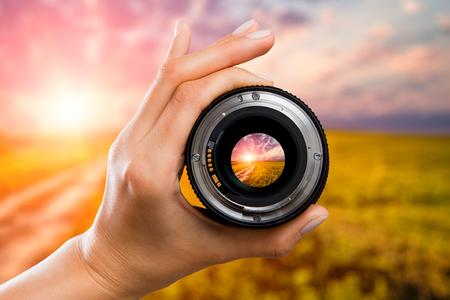fotografie camera fotograaf lens door veld zonsondergang zonsopgang zon wolkenhemel video foto digitale glas hand wazig aandacht mensen concept - stock