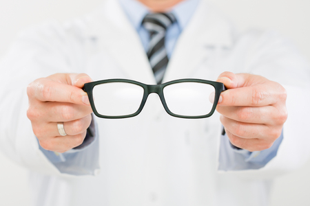 medical occupation: doctor optician glasses optometrist optical store new vision men shop closeup occupation medical medicine eyeglasses lens human hand caucasian concept - stock image