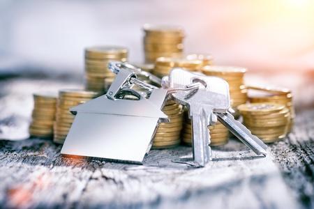 家の形をしたキーホルダーと木製のテーブルの上のコインに家の鍵。不動産や賃貸の家のコンセプトです。