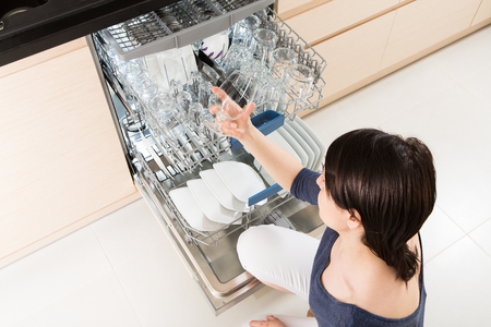 dishwasher: Woman using a dishwasher in a modern kitchen. Domestic appliance.