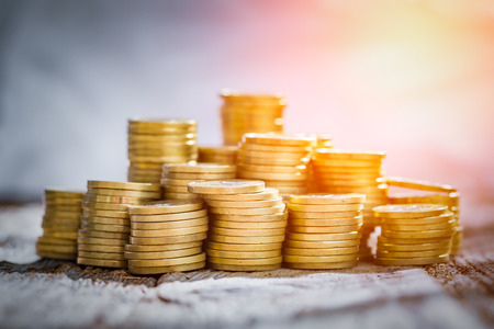golden coin money stack save savings profit wooden table - stock image