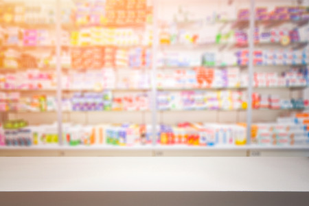 counter store table pharmacy background shelf blurred blur focus drug medical shop drugstore medication blank medicine pharmaceutics concept - stock image Stock Photo - 64977759
