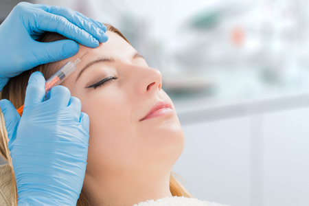 Botulinum-Toxinfrau füllt Badekurortgesichtsjunge-Behandlungsspritze ein, die Einspritzungshaut-Lippenkonzept einspritzt - Archivbild Standard-Bild