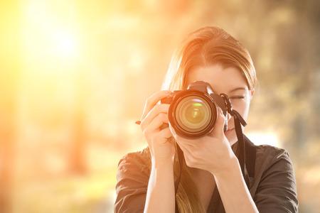 カメラで彼女の顔を覆っている写真家の肖像画。