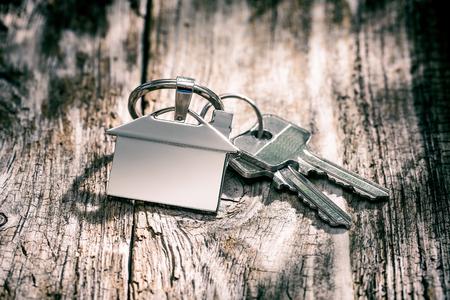 木製のテーブルで家の形をしたキーチェーンに家の鍵。不動産や賃貸の家のコンセプトです。