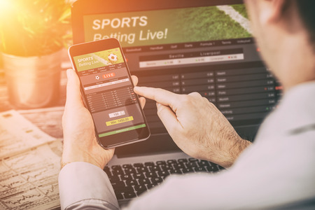 over the shoulder view: betting bet sport phone gamble laptop over shoulder soccer live home website concept - stock image