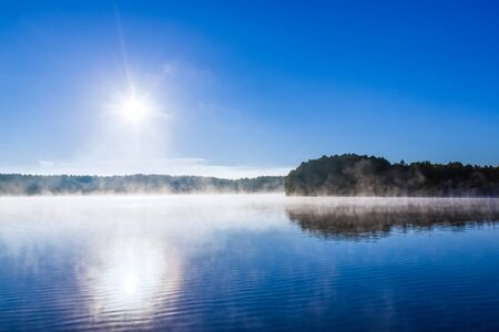 lake fog forest water sky sunlight sunrise mist landscape sun blue light design backgrounds - stock image  Stock Photo