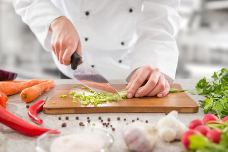 hombre rojo: cocinero que cocina el alimento de la cocina de corte cocinero del restaurante manos hombre un hotel preparación cuchillo masculina preparan fresco concepto - Imagen